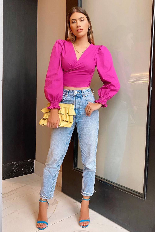 cropped rosa com mangas bufantes, calça jeans reta e sandália de duas tiras