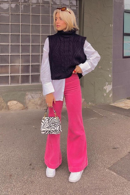 sobreposição com camisa branca, olete preto de tricô, calça rosa e tênis branco