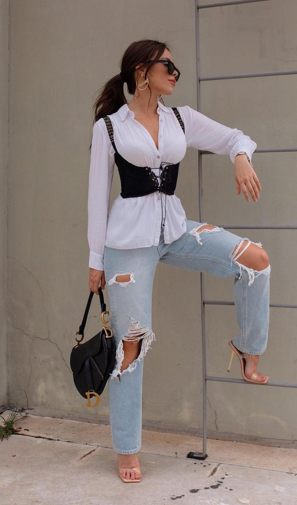 corset preto sobrepondo a camisa branca calça jeans destroyed, e sandália com tira de plástico