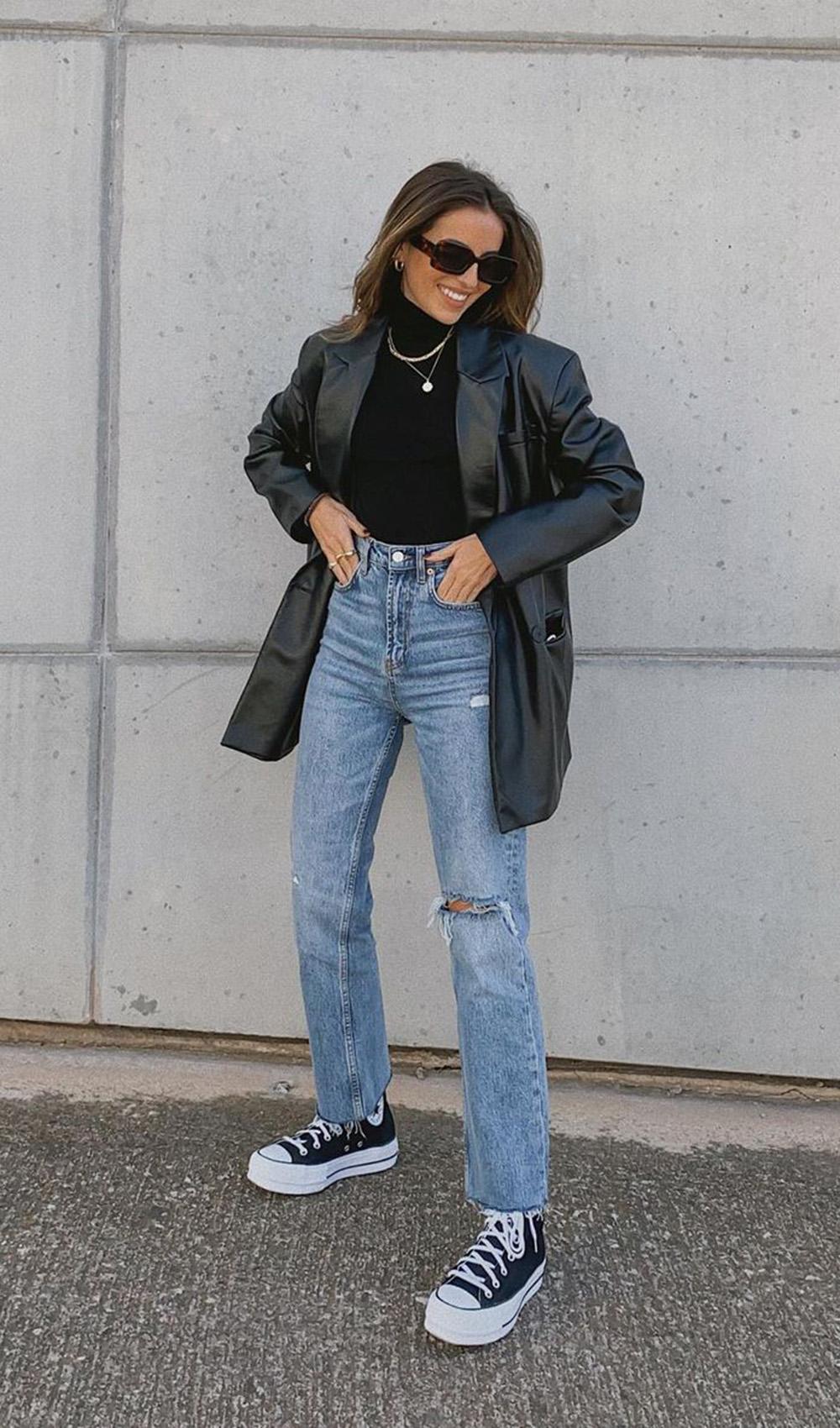 jaqueta de couro, blusa de gola alta preta, calça jeans reta e tênis all star