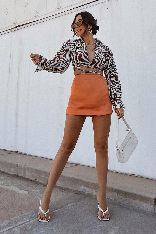 camisa de zebrinha com minissaia laranja e sandália de tiras