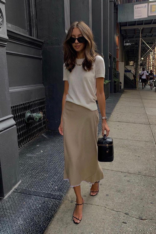 t-shirt branca, saia bege e sandália de tiras