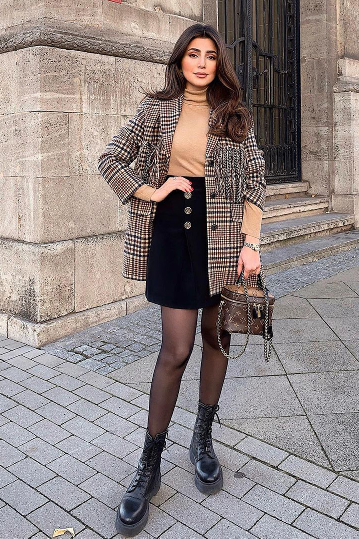 Look com meia-calça, blazer xadrez e blusa de gola alta e minissaia