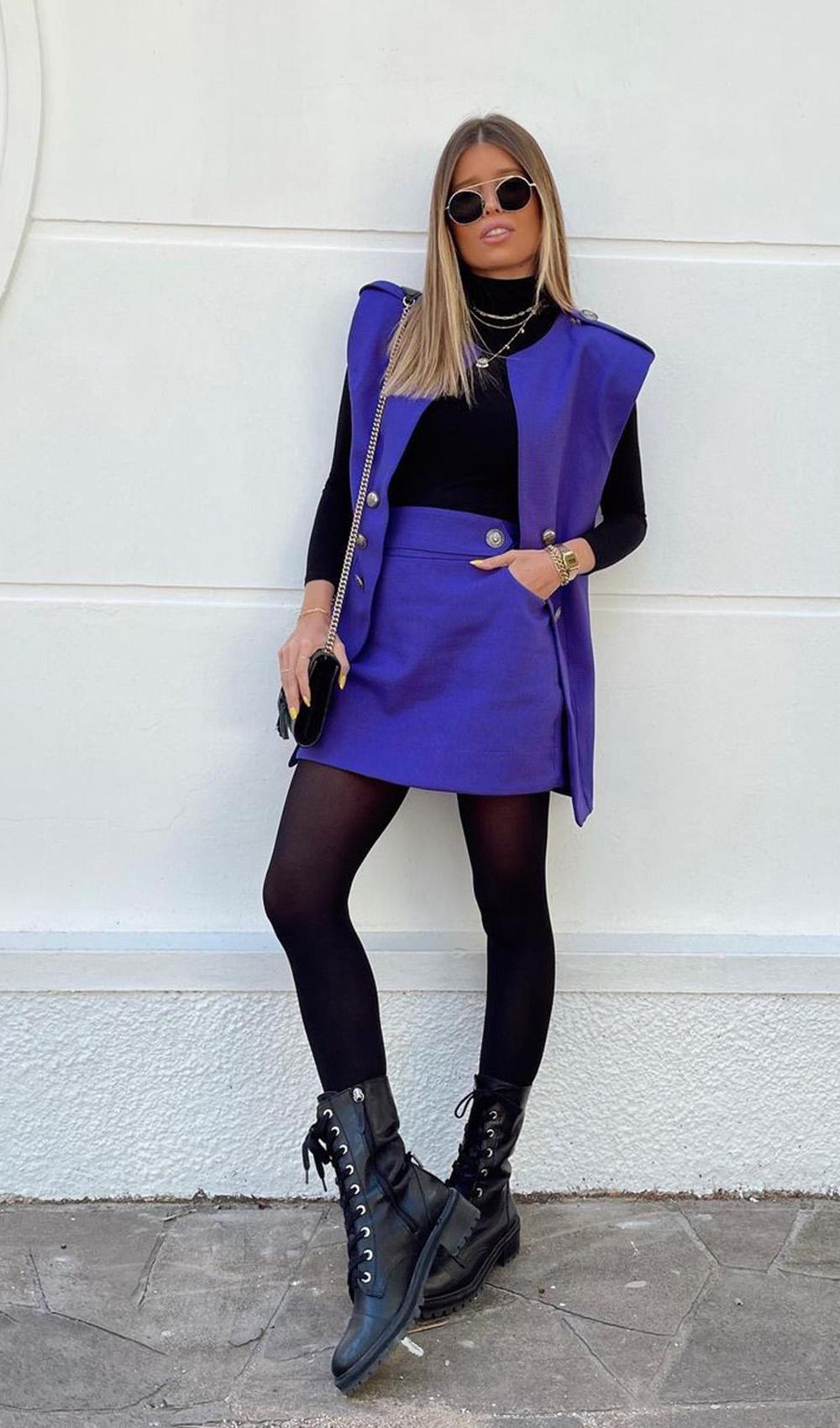 conjuntinho azul com saia e colete, blusa de gola alta e coturno