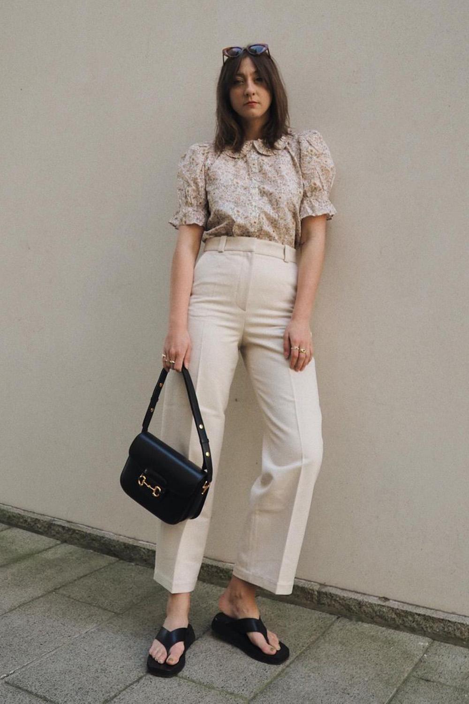 camisa floral, calça de alfaiataria branca, sandália e bolsa preta