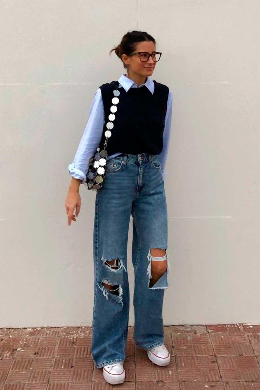sobreposição com camisa azul e colete de tricô preto, calça jeans destroyed e tênis branco