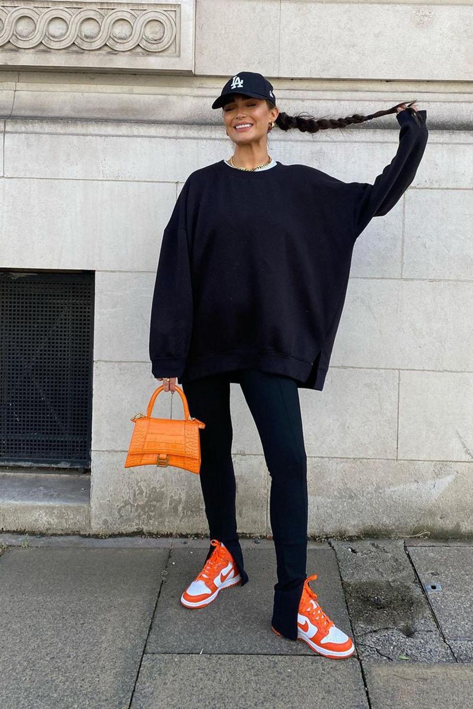 boné no look all black com moletom oversized, calça preta flire, tênis e bolsa laranja
