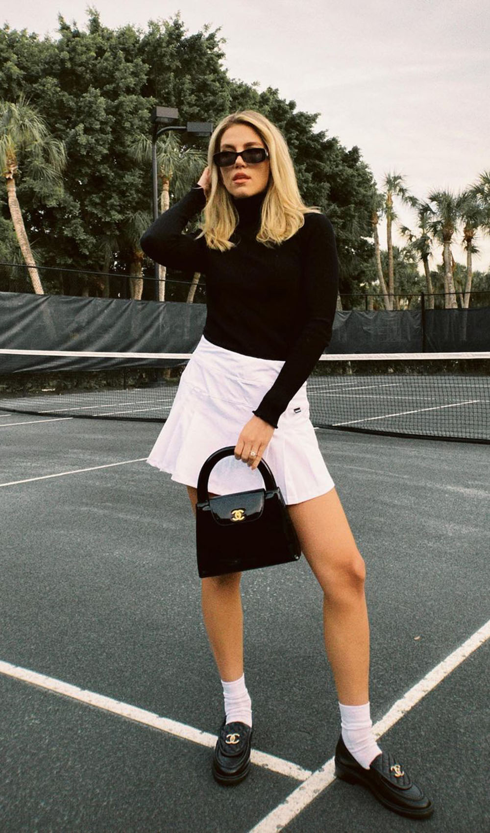 blusa preta de manga, minissaia e bolsa preta