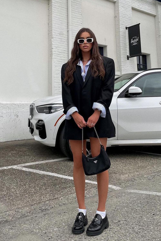 loafer preto com meia barnca, blazer oversized e sobreposição com camisa social oversized