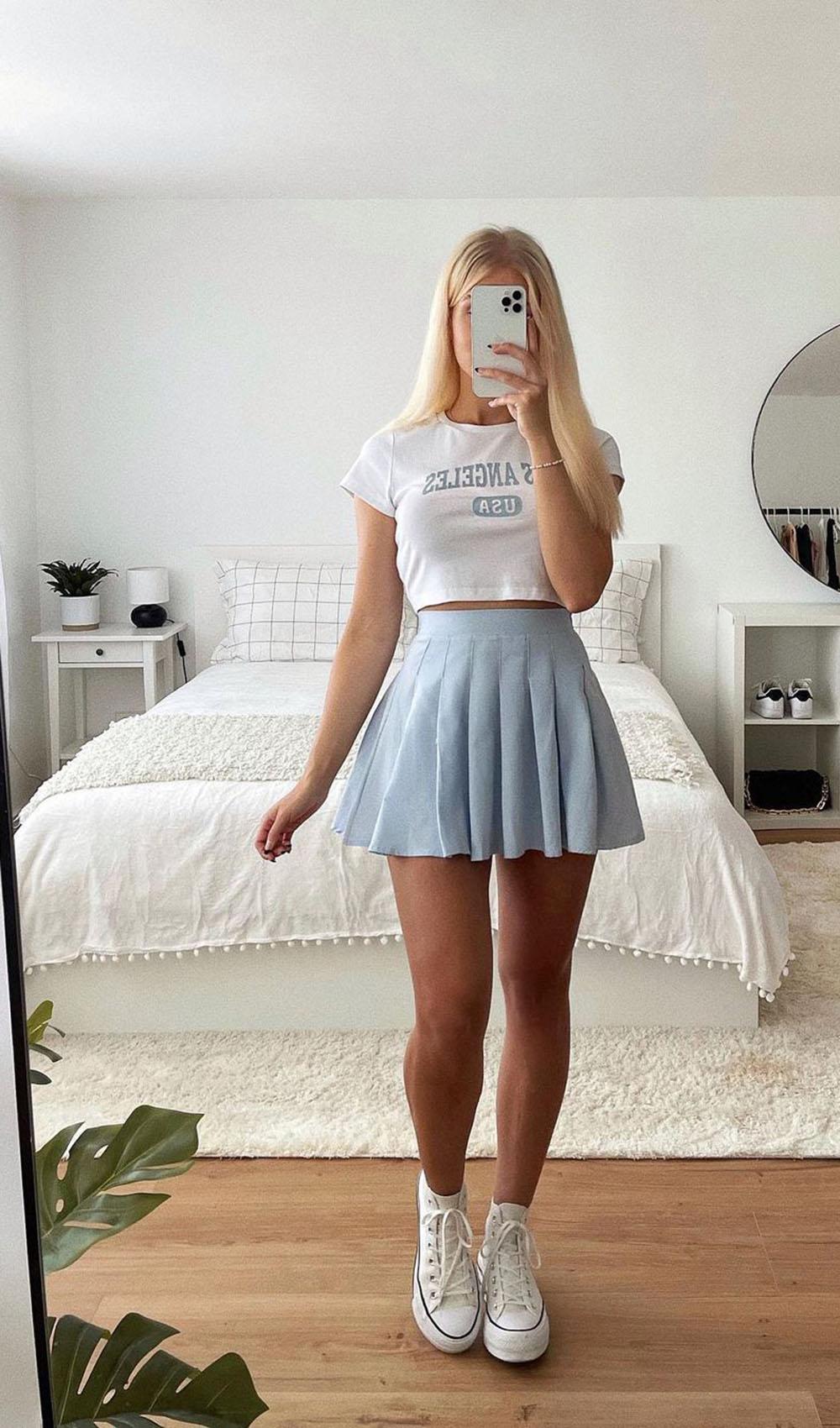 baby tee, saia plissada azul e tênis branco