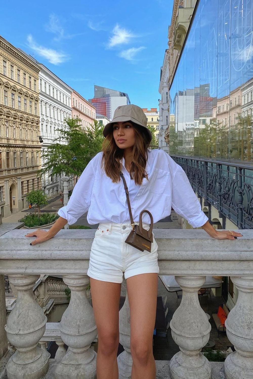 bucket hat, camisa branca, shortinho e minibolsa