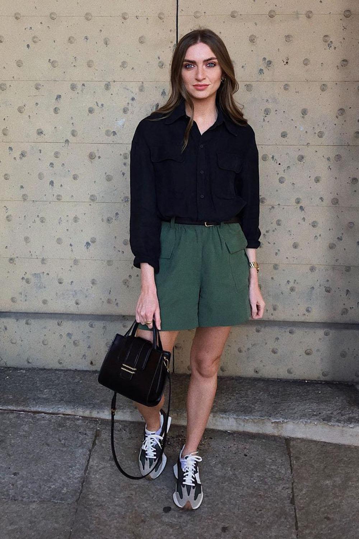 tênis cinza, camisa preta, bermuda verde militar e bolsa box preta