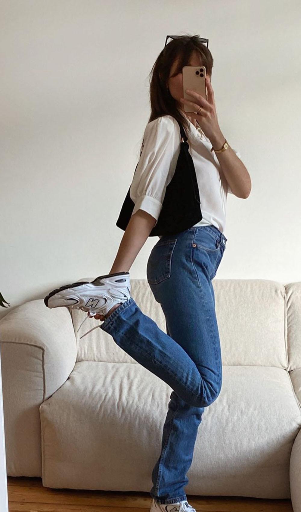 New Balance branco, camisa branca, mom jeans e bolsa baguete preta