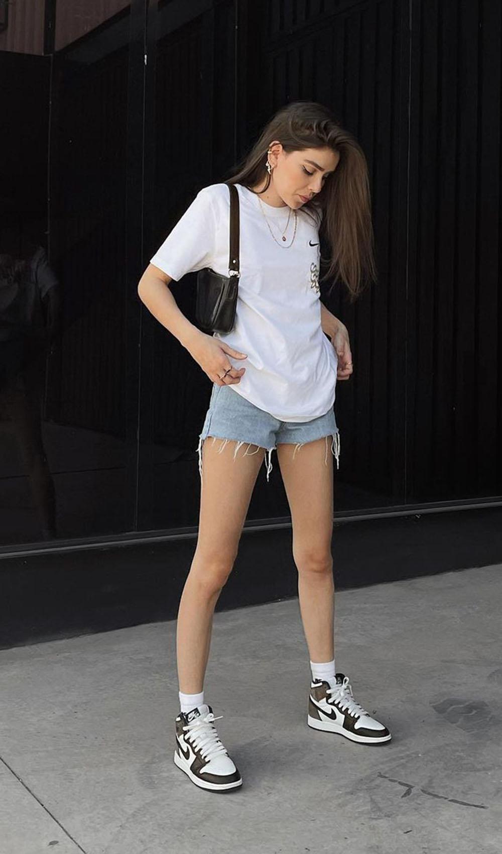 t-shirt branca, short jeans desfiao, bolsa baguete preta e nike jordan