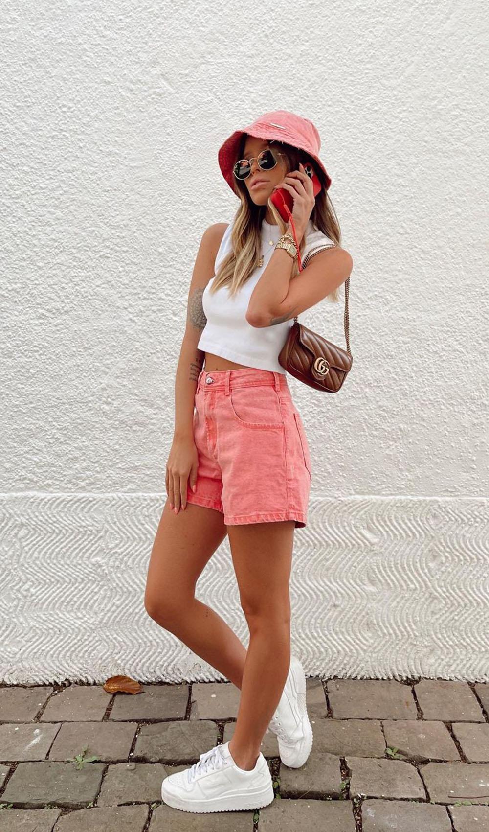 Regata branca com shortinho rosa, bucket hat e tênis branco
