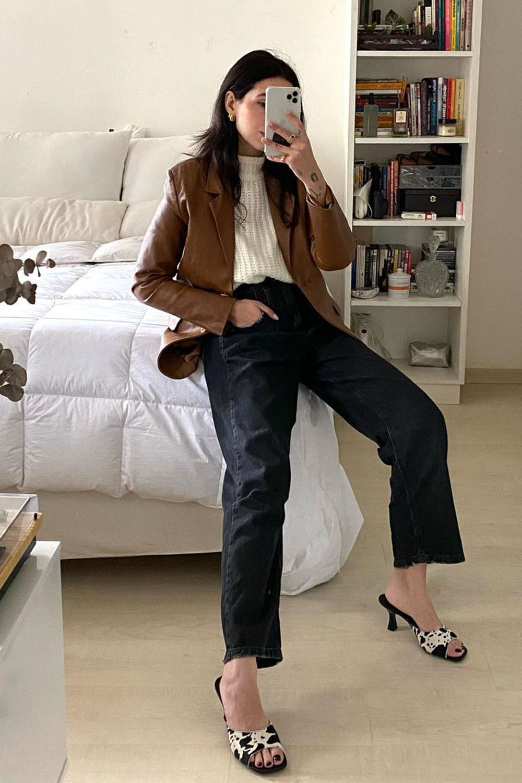 cores neutras, jaqueta de couro marrom, suéter, calça preta e sandália de vaquinha
