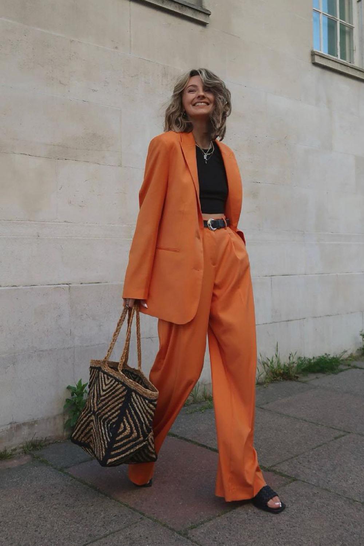 alfaiataria oversized, terninho laranja, blusa preta e rasteirinha