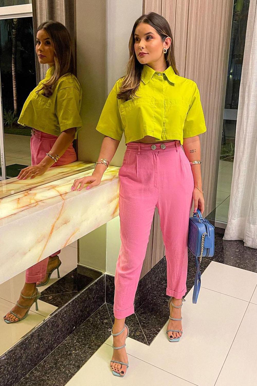 camisa amarela, calça de alfaiataria rosa e sandália de tiras