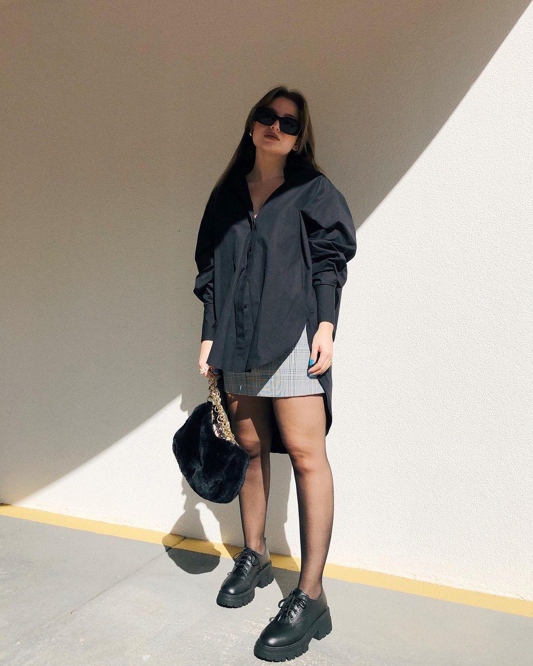 camisa preta com mangas bufantes, minissaia, meia-calça, chunky oxford