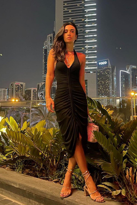 Look com vestido midi preto e sandália de tiras dourada pra jantar