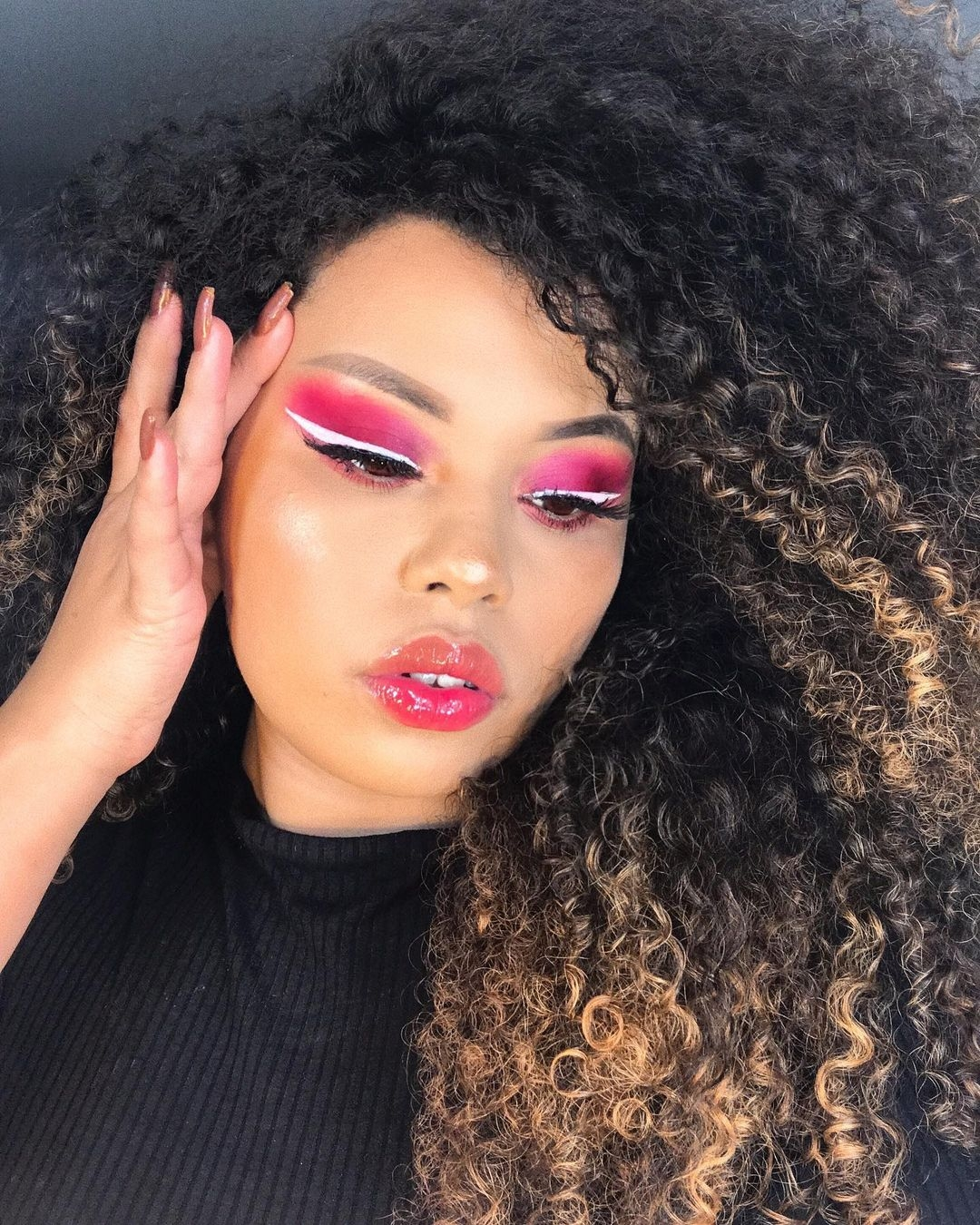 Make colorida rosa com delineado branco, cabelo cacheado iluminado
